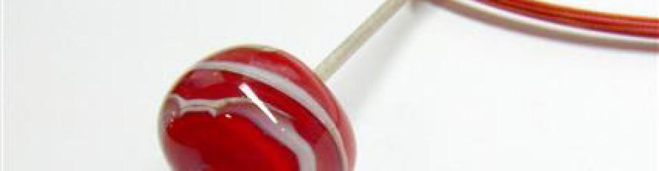Zilveren hanger met rode glaskraal aan gekleurd staalcollier